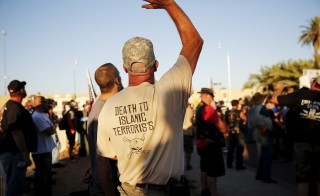 """A demonstrator waves during the """"Freedom of Speech Rally Round II"""" across from the Islamic Community Center in Phoenix, Arizona May 29, 2015. More than 200 protesters, some armed, berated Islam and its Prophet Mohammed outside an Arizona mosque on Friday in a provocative protest that was denounced by counterprotesters shouting """"Go home, Nazis,"""" weeks after an anti-Muslim event in Texas came under attack by two gunmen.  REUTERS/Nancy Wiechec - RTR4Y3NW"""