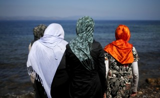 Afghan refugees are seen on a beach, moments after arriving on a dinghy on the Greek island of Lesbos, September 15, 2015. Two decades of frontier-free travel across Europe unraveled on Monday as countries re-established border controls in the face of an unprecedented influx of migrants, which broke the record for the most arrivals by land in a single day. REUTERS/Alkis Konstantinidis - RTS18LD