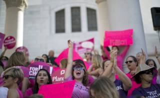 "Activist Sarah Weismer chants during a rally in support of Planned Parenthood on ""National Pink Out Day"" on the steps of City Hall in Los Angeles, Sept. 29. With a deeper-than-ever split between Republicans and Democrats over abortion, activists on both sides of the debate foresee a 2016 presidential campaign in which the nominees tackle the volatile topic more aggressively than in past elections. Photo by Mario Anzuoni/Reuters"