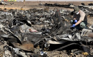 A military investigator from Russia stands near the debris of a Russian airliner at its crash site at the Hassana area in Arish city, north Egypt, November 1, 2015. Egyptian authorities have detained two employees of Sharm al-Sheikh airport in connection with the downing of a Russian jet on October 31, killing all 224 people on board, two security officials said on November 17, 2015. Picture taken November 1, 2015. REUTERS/Mohamed Abd El Ghany - RTS7I1S