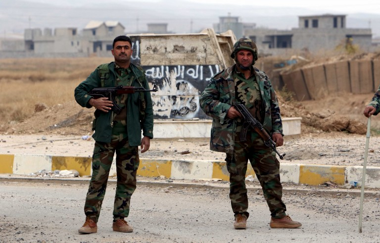 Kurdish peshmerga forces stand in the street after Yazidi people loot houses in the town of Sinjar, Iraq November 16, 2015. Before it was overrun by Islamic State, Sinjar and the surrounding villages were home to about 200,000 people, mainly Kurdish and Arab Muslims - both Sunni and Shi'ite - as well as Christians and Yazidis, a faith that combines elements of several ancient Middle Eastern religions. Now the town is largely deserted. But in a row of houses used by Islamic State fighters, there were signs of recent occupation: a smell of rotting food, and foam mattresses and pillows laid on the floor. Picture taken November 16 2015. REUTERS/Azad Lashkari - RTS7Y6W