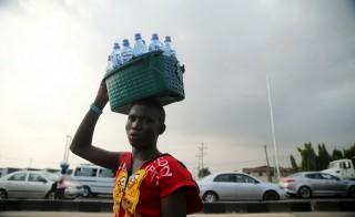 A man sells water along a road in Lagos, Nigeria, November 20, 2015.  REUTERS/Akintunde Akinleye - RTS86RC
