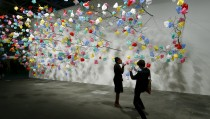 "Visitors take a picture in front of the installation ""Plastic Tree"" by Cameroonian artist Pascale Marthine Tayou at the Art Unlimited exhibition at the Art Basel fair in Basel June 16, 2015. Founded by gallerists in 1970, the Art Basel is an international art show which is held annually in Basel, Hong Kong and Miami Beach. REUTERS/Arnd Wiegmann  FOR EDITORIAL USE ONLY. NOT FOR SALE FOR MARKETING OR ADVERTISING CAMPAIGNS  - RTX1GRMJ"