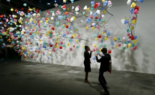 """Visitors take a picture in front of the installation """"Plastic Tree"""" by Cameroonian artist Pascale Marthine Tayou at the Art Unlimited exhibition at the Art Basel fair in Basel June 16, 2015. Founded by gallerists in 1970, the Art Basel is an international art show which is held annually in Basel, Hong Kong and Miami Beach. REUTERS/Arnd Wiegmann  FOR EDITORIAL USE ONLY. NOT FOR SALE FOR MARKETING OR ADVERTISING CAMPAIGNS  - RTX1GRMJ"""