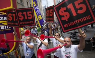 People celebrate the passage of the minimum wage for fast-food workers by the New York State Fast Food Wage Board during a rally in New York July 22, 2015.  New York state moved on Wednesday to raise the minimum wage for fast-food workers to $15 an hour in New York City by the end of 2018 and in the rest of the state by mid-2021. The New York Wage Board, a panel formed by New York governor Cuomo to review the minimum wage for the state's 180,000 fast-food workers, voted unanimously on the pay increase, which would affect some 180,000 workers statewide.  REUTERS/Brendan McDermid  - RTX1LEYV