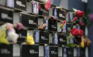 """Flowers are placed on a memorial wall commemorating the late former South and North Korean """"comfort women"""" at the War and Women's Human Rights Museum"""" in Seoul. South Korea and Japan reached a breakthrough settlement Monday to resolve a decades-long dispute regarding Korean women forced into sex slavery by the Japanese military during World War II. Photo by Kim Kyung-Hoon/Reuters"""