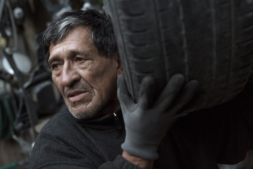 A worker moves a tire through a workshop in the Willets Point area of Queens in New York October 29, 2015. Willets Point, also known as the Iron Triangle, is an industrial precinct that sits in the shadow of Citi Field, home of the New York Mets baseball team. Many businesses within Willets Point employ a largely immigrant workforce. The area features a large number of corrugated iron structures and, according to the New York City Economic Development Corporation, floods easily due to geography and limited storm water infrastructure. Willets Point tenants have been fighting the City of New York, who wish to carry out further relocations of businesses in the precinct and redevelop the area, local media sources reported. Picture taken October 29, 2015. REUTERS/Andrew Kelly - RTX1UA9Y