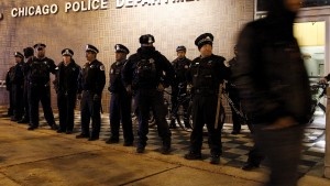 A protester walks past a line of police officers standing guard in front of the District 1 police headquarters in Chicago, Illinois November 24, 2015. Jason Van Dyke, a white Chicago policeman who fatally shot Laquan McDonald, a black teenager, was charged with murder on Tuesday, hours before authorities released a long-awaited video that shows the youth walking away from officers as he is slain by a volley of 16 gunshots. The graphic footage of last year's shooting, taken from a camera mounted on the dashboard of a police car and made public under orders from a judge, sparked mostly peaceful street demonstrations in Chicago on Tuesday.  REUTERS/Frank Polich - RTX1VPMX