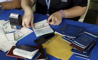 A Costa Rican immigration officer sticks a visa extension to last for 15 more days into a Cuban passport in Liberia, Costa Rica, November 26, 2015. Thousands of Cubans remain stuck on the Costa Rican side of the border with Nicaragua after Managua refused at a regional summit on Tuesday to open its doors to a wave of migrants heading for the United States. Fearing the recent rapprochement between Havana and Washington could end preferential U.S. policies for Cuban migrants, thousands of people from the Communist-ruled island have been crossing into South America and traveling through Central America hoping to reach U.S. soil.   REUTERS/Juan Carlos Ulate  - RTX1W0S6