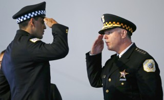 Chicago Police Superintendent Garry McCarthy (R) returns a salute to an unnamed recruit during a recruitment graduation ceremony in Chicago, Illinois on April 21, 2014. Chicago's police chief was ousted on December 1, 2015 following days of unrest over video footage showing the shooting of a black teenager and the filing of murder charges against a white police officer in the young man's death. Picture taken on April 21, 2014.    REUTERS/Jim Young - RTX1WPLG