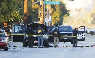 FBI and police investigator are seen around a vehicle in which two suspects were shot following a mass shooting in San Bernardino, California December 3, 2015. Authorities on Thursday were working to determine why Syed Rizwan Farook, 28, and Tashfeen Malik, 27, who had a 6-month-old daughter together, opened fire at a holiday party of his co-workers in Southern California, killing 14 people and wounding 17 in an attack that appeared to have been planned.   REUTERS/Mike Blake - RTX1X0X3