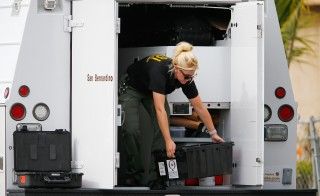 A Sheriff's Office Crime Scene Iinvestigator unloads equipment at the scene of the investigation around an SUV where two suspects were shot by police following a mass shooting in San Bernardino, California December 3, 2015.  Authorities on Thursday were working to determine why Syed Rizwan Farook 28, and Tashfeen Malik, 27, opened fire at a holiday party of his co-workers in Southern California, killing 14 people and wounding 17 in an attack that appeared to have been planned. REUTERS/Mike Blake - RTX1X2P8