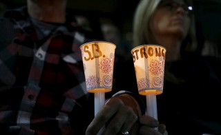 Attendees hold candles with a hand written message as they reflect on the tragedy of Wednesday's attack during a candlelight vigil in San Bernardino, California. The Dec. 3 shooting in San Bernardino threw politicians off their talking points as more details about the suspects -- stockpiling weapons, possible links to extremists -- came to light. Photo by Mike Blake/Reuters