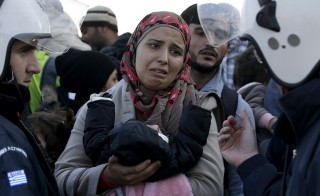 A Syrian refugee woman holding her baby reacts in front of a Greek police cordon whille trying to reach a narrow border crossing into Macedonia near the Greek village of Idomeni December 4, 2015. REUTERS/Yannis Behrakis - RTX1X8W9