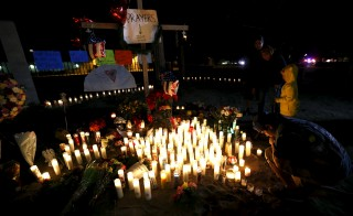 "People stand by a pop-up memorial in San Bernardino, California on Friday, following Wednesday's attack. Authorities are investigating the San Bernardino, California, shooting as an ""act of terrorism"", Federal Bureau of Investigation assistant director David Bowdich said at a news conference on Friday. Photo By Mario Anzuoni/Reuters"