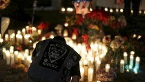"Aidan Solis, 11, kneels by a pop-up memorial in San Bernardino, California December 4, 2015, following Wednesday's attacks. The FBI is investigating the fatal shooting of 14 people in California by a married couple as an ""act of terrorism,"" officials said on Friday, noting the wife was believed to have pledged allegiance to a leader of the militant group Islamic State. REUTERS/Mario Anzuoni - RTX1X9XW"
