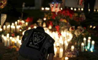 """Aidan Solis, 11, kneels by a pop-up memorial in San Bernardino, California December 4, 2015, following Wednesday's attacks. The FBI is investigating the fatal shooting of 14 people in California by a married couple as an """"act of terrorism,"""" officials said on Friday, noting the wife was believed to have pledged allegiance to a leader of the militant group Islamic State. REUTERS/Mario Anzuoni - RTX1X9XW"""