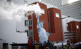 "A replica of the Statue of Liberty is seen with smoke trailing out from its torch during a street parade as part of the ""Global Village of Alternatives"" events held in Montreuil, near Paris, France, December 5, 2015 as the World Climate Change Conference 2015 (COP21) continues at Le Bourget near the French capital. REUTERS/Benoit Tessier - RTX1XB6E"