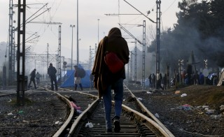 A stranded Pakistani migrant walks away from the Greek-Macedonian border, after failing to cross over, near to the village of Idomeni, Greece December 5, 2015. REUTERS/Yannis Behrakis - RTX1XC9Q
