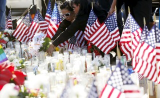 "People leave flowers at a makeshift memorial after last week's shooting in San Bernardino, California, on Dec. 7, 2015. Homeland Security said the department was reviewing its K-1 visa program, known as ""fiancé visas,"" after one of the two shooters in the San Bernardino shooting moved to the United States to marry Syed Farook, her husband and accomplice in the massacre last week. Photo by Patrick T. Fallon /Reuters"