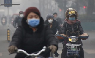 People wearing protective masks ride bicycles in the morning on an extremely polluted day in Beijing, China December 8, 2015. REUTERS/Kim Kyung-Hoon - RTX1XN9E
