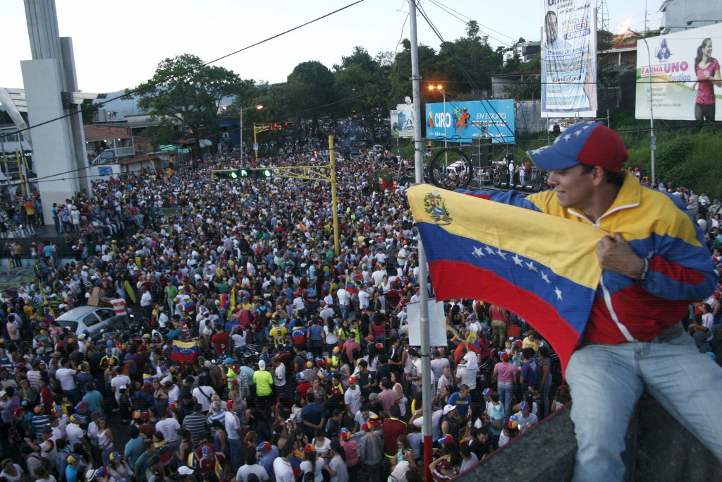 An opposition supporter holds a Venezuelan national flag during a gathering to celebrate the victory of their deputy candidates on a street at San Cristobal in Tachira state, Venezuela December 7, 2015. REUTERS/Carlos Eduardo Ramirez EDITORIAL USE ONLY. NO RESALES. NO ARCHIVE. - RTX1XN9H
