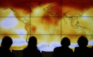 Participants are seen in silhouette as they look at a screen showing a world map with climate anomalies during the World Climate Change Conference 2015 (COP21) at Le Bourget, near Paris, France, December 8, 2015.  REUTERS/Stephane Mahe      TPX IMAGES OF THE DAY  - RTX1XPHY