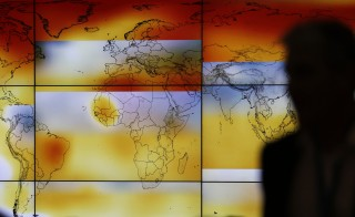 A participant is pictured in front of a screen projecting a world map showing climate anomalies during the World Climate Change Conference 2015 (COP21) at Le Bourget, near Paris, France, December 8, 2015. REUTERS/Stephane Mahe  - RTX1XPN4