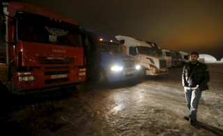 A truck driver stands in front of trucks at a parking lot, as he arrives for a protest against a new fee, in the Moscow region in Russia on December 3. As of last month, the state has started charging a fee for every kilometer that trucks over 12 tons in weight drive over Russian roads. Photo by Reuters and Maxim Zmeyev