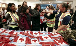 Syrian refugees receive welcome bags at the Toronto Pearson International Airport in Mississauga, Ontario, Canada December 11, 2015. After months of promises and weeks of preparation, the first Canadian government planeload of Syrian refugees landed in Toronto on Thursday, aboard a military aircraft met by Prime Minister Justin Trudeau.     REUTERS/Mark Blinch - RTX1Y6W2