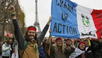 "Environmentalists hold a banner which reads, ""Crank up the Action"" at a protest demonstration near the Eiffel Tower in Paris, France, as the World Climate Change Conference 2015 (COP21) continues near the French capital in Le Bourget, December 12, 2015. Photo by Mal Langsdon/Reuters"