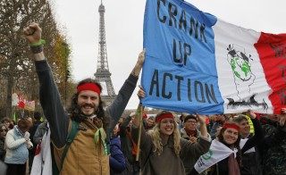 """Environmentalists hold a banner which reads, """"Crank up the Action"""" at a protest demonstration near the Eiffel Tower in Paris, France, as the World Climate Change Conference 2015 (COP21) continues near the French capital in Le Bourget, December 12, 2015. Photo by Mal Langsdon/Reuters"""