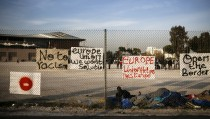 Migrants, who were stranded between Greece and Macedonia, rest next to placards hung on a metal fence, outside the Tae Kwon Do stadium at the southern suburb of Faliro, in Athens, Greece, December 14, 2015.  REUTERS/Alkis Konstantinidis - RTX1YMFW