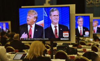 Republican U.S. presidential candidates businessman Donald Trump (L) and  former Governor Jeb Bush (R) are seen debating on video monitors in the debate press room during the Republican presidential debate in Las Vegas, Nevada December 15, 2015. Photo by David Becker/Reuters