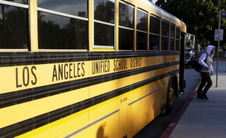 A student exits a bus as he arrives at Venice High School in Los Angeles, California December 16, 2015. Classes resume today in Los Angeles, the second largest school district in the United States,  after they were closed on Tuesday after officials reported receiving an unspecified threat to the district and ordered a search of all schools in the city. REUTERS/Jonathan Alcorn - RTX1YZEW
