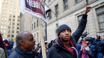 Moments before his arrest, activist Darius Rosebrough (R) leads a protest in front of the courthouse in Baltimore, December 16, 2015. A Maryland judge declared a mistrial on Wednesday in the trial of the first of six Baltimore police officers charged in the death of Freddie Gray, whose killing sparked riots and arson in the city in April. The jury had deliberated for 16 hours on whether the officer, William Porter, was guilty of involuntary manslaughter in Gray's death from injuries suffered while in police custody. After it reported it was unable to reach a verdict, Baltimore City Circuit Court Judge Barry Williams issued his ruling. REUTERS/Bryan Woolston - RTX1Z0WR