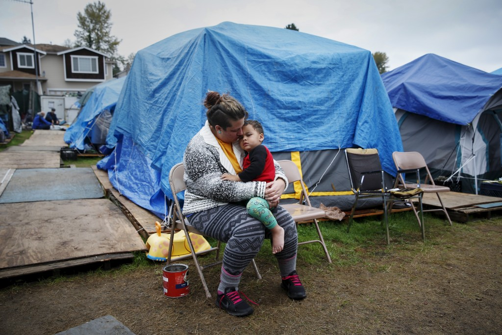 "Kadee Ingram, 28, holds her son Sean, 2, at SHARE/WHEEL Tent City 3 outside Seattle, Washington October 13, 2015. Ingram lost her job, and soon afterwards her partner Renee lost her job. ""It got (to) the point where we couldn't get a job fast enough and we lost our apartment,"" Ingram said. ""Coming here, we really like it, being outside especially, we feel safe. We wish we would have known about it sooner.""  REUTERS/Shannon Stapleton PICTURE 17 OF 35 - SEARCH ""STAPLETON TENTS"" FOR ALL IMAGES TPX IMAGES OF THE DAY      TPX IMAGES OF THE DAY      - RTX1Z3JC Related words: inequality, poverty, poor, homeless"