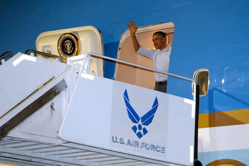 U.S. President Barack Obama waves as he and his family arrive via Air Force One at Joint Base Pearl Harbor-Hickam in Honolulu, Hawaii Saturday.   Photo By Jonathan Ernst/Reuters
