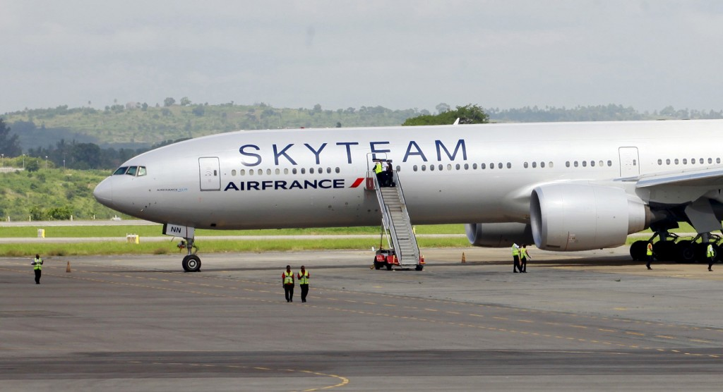 Airport workers are seen near the Air France Boeing 777 aircraft that made an emergency landing is pictured at Moi International Airport in Kenya's coastal city of Mombasa, December 20, 2015. The Air France flight from Mauritius diverted and made an emergency landing at Kenya's port city of Mombasa after a suspicious device was found in a toilet, Kenya's head of police and the airline said on Sunday. Photo by Joseph Okanga/Reuters