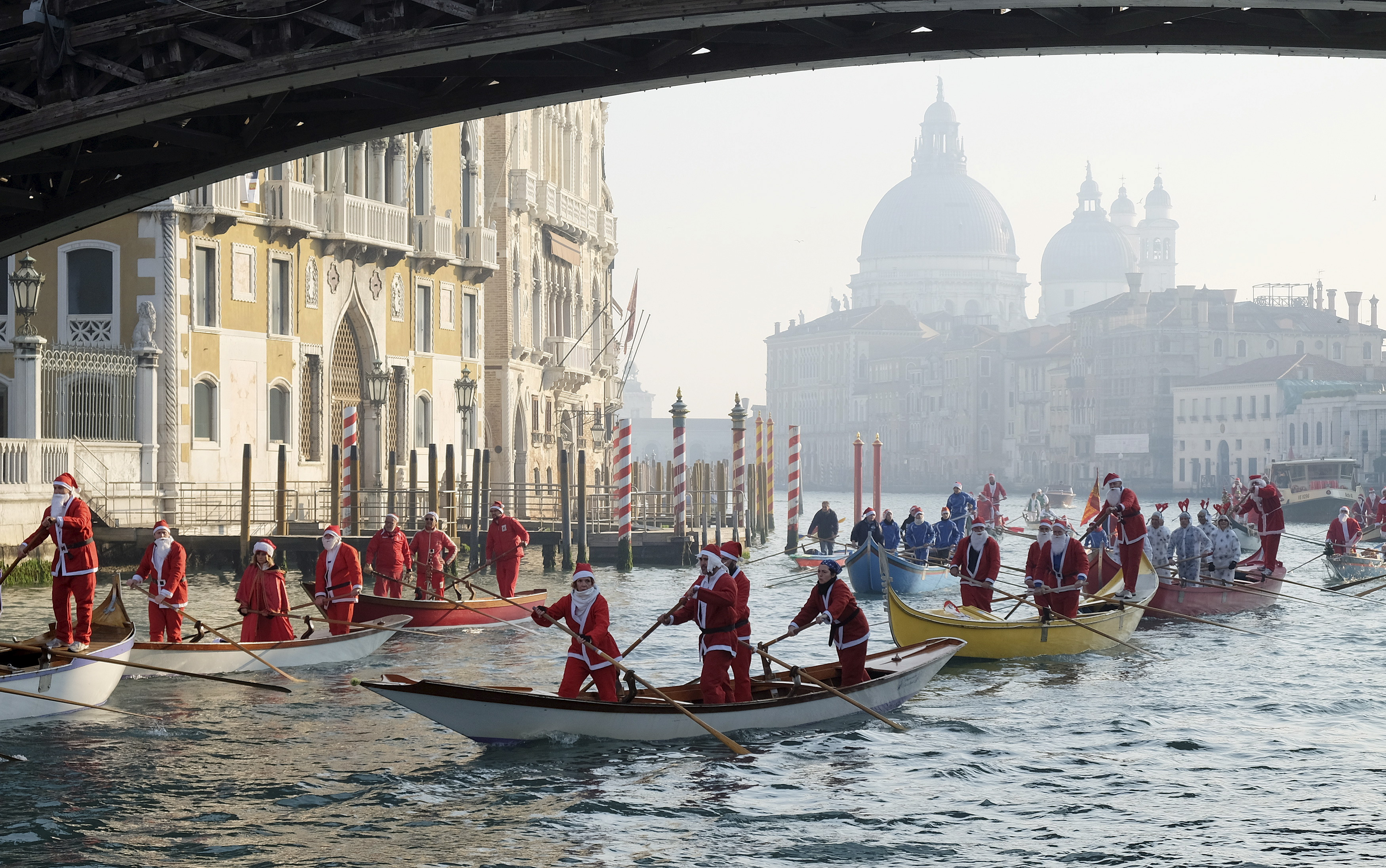 People dressed as Santa Claus row boats on Venice's Grand Canal, in northern Italy, December 20, 2015. Photo by: Manuel Silvestri/Reuters