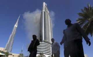 People walk as plumes of smoke rise from The Address Downtown Dubai hotel and residential block, a day after it caught fire on New Year's Eve, in Dubai. Photo by Reuters