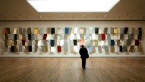 """A visitor walks towards Ellsworth Kelly's """"Sculpture For a Large Wall"""" of anodized aluminum (1957) in the newly renovated Museum of Modern Art in New York City, November 15, 2004. The new museum, which stands between 53rd and 54th streets in Midtown Manhattan, was designed by Japanese architect Yoshio Taniguchi and nearly doubles the capacity of the former building. The Museum encompasses 630,000 square feet on six floors and cost $425 million to build. The reopening of the Museum to the public on November 20 will commemorate its 75th anniversary. - RTXN1TF"""