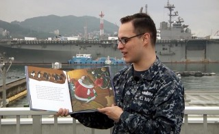 "Seaman James Hunt with the U.S. Navy reads part of the holiday poem, ""A Visit from St. Nicholas,"" by Clement Clarke Moore"