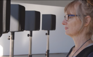 Janet Cardiff stands in front of a sound sculpture. Photo courtesy of KQED