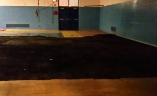 Black tarp covers damaged gym floor at Spain Elementary-Middle School in Detroit. Photo by Janet Bass, AFT.