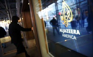 The logo for Al Jazeera America is displayed outside of the cable news channel's offices on January 13, 2016 in New York City. Al Jazeera America, which debuted in August 2013,  announced today that they are shutting down. Employees of the struggling news network known as AJAM were informed of the decision during an all-hands staff meeting on Wednesday afternoon.  Photo by Spencer Platt/Getty Images