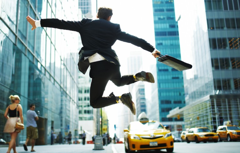 Businessman jumping for joy on city street. Credit: Andy Ryan/Getty Images