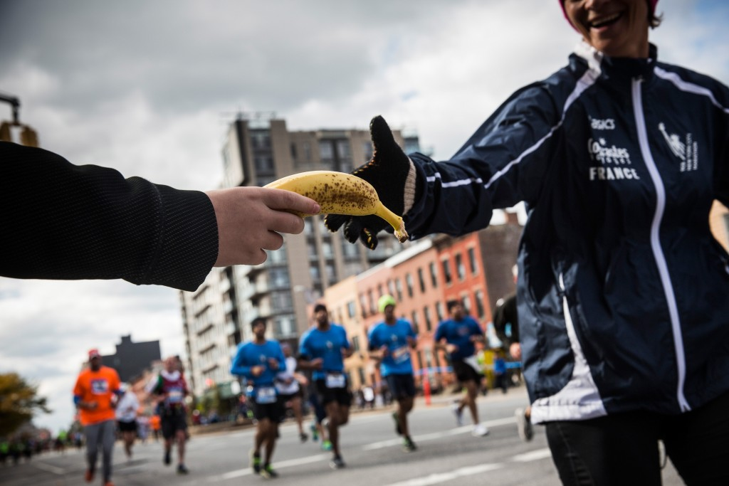 A volunteer hands out bananas to runners participating in the TCS New York City Marathon on November 2, 2014. Photo by Andrew Burton/Getty Images.