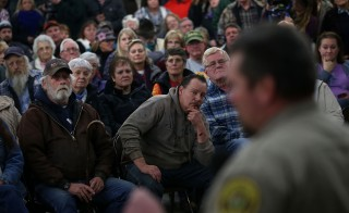 Harney County residents in rural Oregon look on as Harney County Sheriff David Ward speaks during a community meeting at the Harney County fairgrounds in Burns, Oregon. Jan. 6, 2016. Hundreds of Harney County residents attended a community meeting to express frustration and support over an armed anti-government militia group that continues to occupy the Malheur National Wildlife Headquarters. Photo by Justin Sullivan/Getty Images
