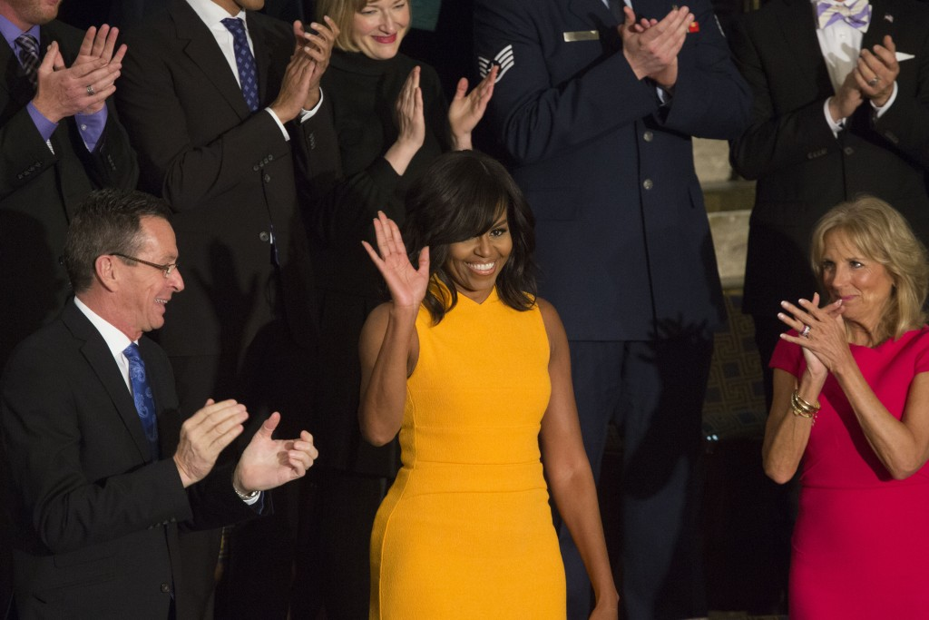 First Lady Michelle Obama, center, waves to the crowd as she is introduced during U.S. President Barack Obama's State of the Union address on Jan. 12, 2016. Photo by Drew Angerer/Bloomberg via Getty Images.